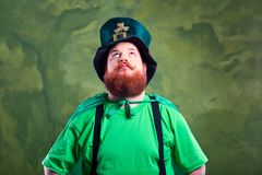 A fat man with a beard in St. Patrick`s suit is smiling. A fat man with a beard in St. Patrick`s suit is smiling on a green background Royalty Free Stock Photos