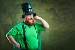 A fat man with a beard in St. Patrick`s suit is smiling. A fat man with a beard in St. Patrick`s suit is smiling on a green background Royalty Free Stock Image