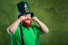 A fat man with a beard in St. Patrick`s suit is smiling. Royalty Free Stock Photography