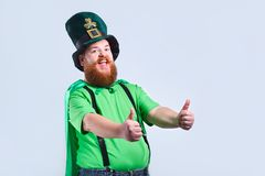 A fat man with a beard in St. Patrick`s suit is smiling with a m. Ug of beer on a gray background Royalty Free Stock Photography
