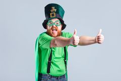 A fat man with a beard in St. Patrick`s suit is smiling with a m. Ug of beer on a gray background Royalty Free Stock Photo