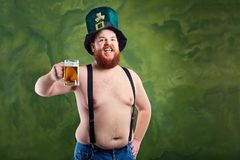 A fat man with a beard in St. Patrick`s suit is smiling with a m. Ug of beer on a green background Stock Photography