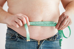 Fat man belly with measuring tape. Lose weight concept. Royalty Free Stock Photo
