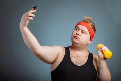 Fat man with big belly, holding dumbbell, doing selfie on grey background royalty free stock photos