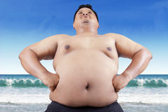 Fat man with big stomach on beach Royalty Free Stock Photos
