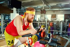 A fat man on a bike simulator in the gym stock images