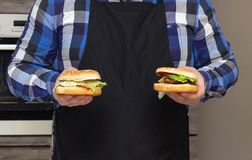 Fat man in a black apron holds two hamburger, close-up, copy space, fast food stock photography