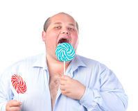 Fat Man in a Blue Shirt, Eating a Lollipop Royalty Free Stock Image