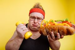 Fat man choise between sport and fastfood stock photo