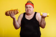 Fat man choise between sport and fastfood royalty free stock photography