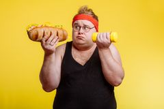 Fat man choise between sport and fastfood royalty free stock image