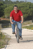 Fat man cycling on the countryside Stock Images
