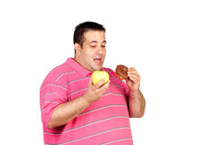 Fat man deciding between an apple and a sweet Royalty Free Stock Photography