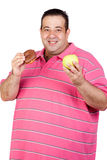 Fat man deciding between a candy and an apple Stock Image