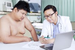 Fat man and doctor looking at medical result. Portrait of a fat men and his doctor looking at the medical result on the laptop in hospital Stock Image
