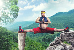 Fat man does the splits. Fat sportsman does the splits in the mountains Stock Images