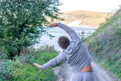 Fat man doing warm-up in nature. Fresh air, sport and a healthy lifestyle stock image