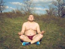 Fat man doing yoga Stock Image