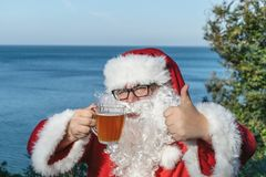 Fat man in glasses dressed as Santa drinking beer on the ocean. Funny, drunk and happy. Fat man dressed as Santa drinking beer on the ocean stock photography