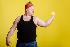Fat man with dumbbell on yellow background. Motivation for fat people. Fat man wearing black shirt exercising with dumbbells and looking at biceps stock photography
