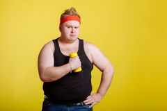 Fat man with dumbbell on yellow background. Motivation for fat people. Fat man wearing black shirt exercising with dumbbells and looking at camera stock image