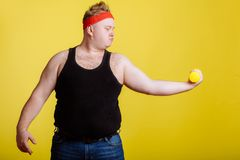Fat man with dumbbell on yellow background. Motivation for fat people. Thick fat man with dumbbell on yellow background. Motivation for fat people. black shirt royalty free stock photo