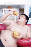 Fat man eating burgers on the sofa. Image of a fat man holding two burgers while sitting on the red sofa at home Stock Photo