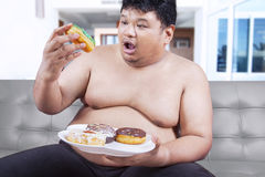 Fat man eating donuts Stock Image
