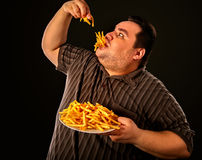 Fat man eating fast food french fries for overweight person. Diet failure of fat man eating fast food . Overweight person who spoiled healthy food by eating Stock Images