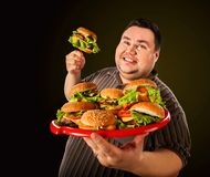 Fat man eating fast food hamberger. Breakfast for overweight person. royalty free stock photo