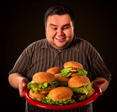 Fat man eating fast food hamberger. Breakfast for overweight person. Fat man eating fast food hamberger and carries treat for friends on tray. Breakfast for stock photo
