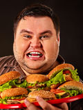 Fat man eating fast food hamberger. Breakfast for overweight person. stock photos