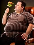 Fat man eating fast food hamberger. Breakfast for overweight person. Stock Images