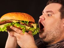 Fat man eating fast food hamberger. Breakfast for overweight person. Diet failure of fat man eating fast food hamberger. Happy smile overweight person who royalty free stock photos