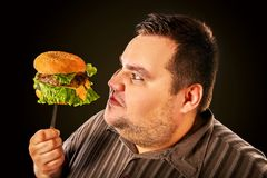 Fat man eating fast food hamberger. Breakfast for overweight person. Man eating fast food. Overweight person eating huge hamburger on fork. People not going to stock photo