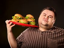Fat man eating fast food hamberger. Breakfast for overweight person. Fat man eating fast food hamberger and carries treat for friends on tray. Breakfast for stock images