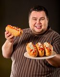 Fat man eating fast food hot dog. Breakfast for overweight person. Royalty Free Stock Photo