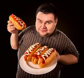 Fat man eating fast food hot dog. Breakfast for overweight person. stock photos