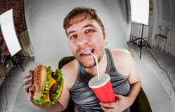 Fat man eating hamburger Stock Photos