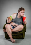 Fat man eating hamburger Royalty Free Stock Images