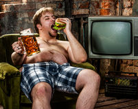 Fat man eating hamburger. Seated on armchair Royalty Free Stock Photography