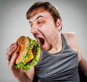 Fat man eating hamburger Royalty Free Stock Photos