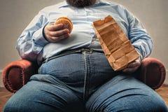 Fat man eating hamburger royalty free stock image