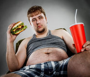 Fat man eating hamburger. Seated on armchair. Style fast food Royalty Free Stock Image