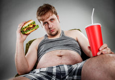 Fat man eating hamburger Stock Photography