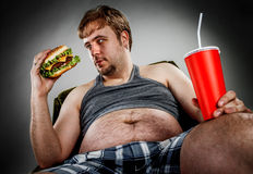 Fat man eating hamburger. Seated on armchair. Style fast food Royalty Free Stock Photography