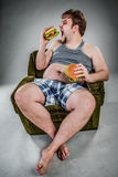 Fat man eating hamburger Stock Photo