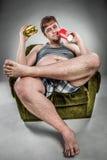 Fat man eating hamburger Stock Photos
