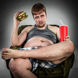 Fat man eating hamburger. Seated on armchair. Style fast food Stock Photo