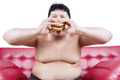 Fat man eating hamburger 1 Royalty Free Stock Photography